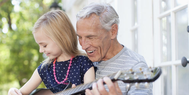 man and granddaughter playing guitar